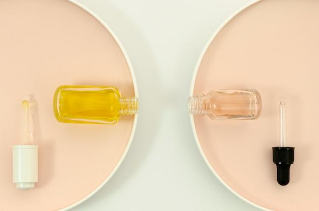 Botellas de maquillaje con pipetas sobre fondo beige y blanco