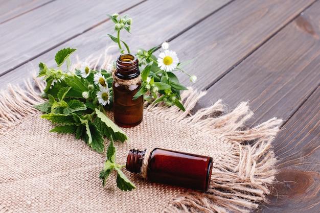 Botellas marrones con aceites, vegetación y flores se encuentran en una servilleta marrón