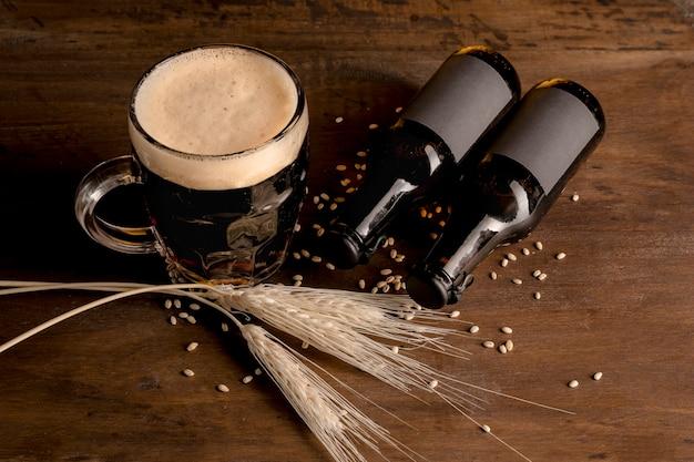 Botellas marrones de cerveza con vaso de cerveza en la mesa de madera