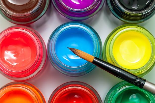 Botellas multicolores poster color y pincel sobre un fondo blanco pinturas aisladas en contenedores vista superior copyspace