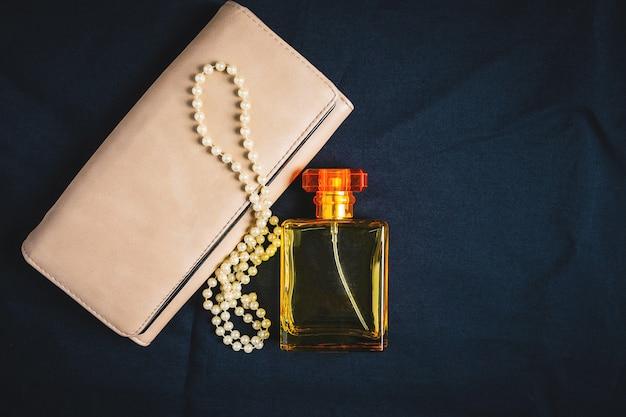 Botellas de perfume y bolsos de mujer con hermosas joyas.