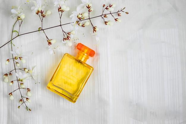 Botellas de perfume y flores sobre un hermoso fondo blanco