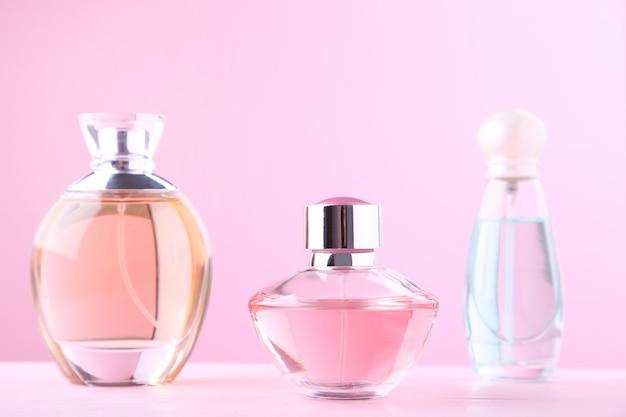 Botellas de perfume en el fondo de color rosa, vista desde arriba