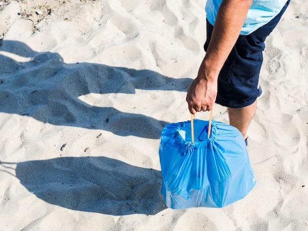 Botellas de plástico en bolsa azul por hombre de pie sobre la arena