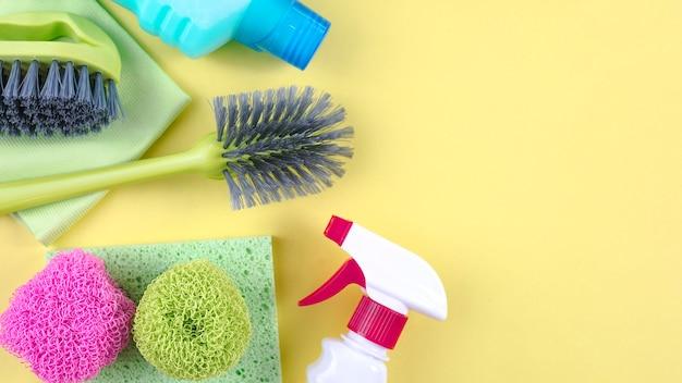 Botellas de plástico, esponja y pincel sobre fondo amarillo