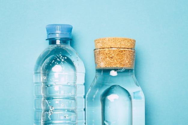 Botellas de plástico y vidrio para agua sobre un fondo azul, una alternativa