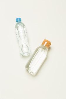Botellas de plástico y vidrio para agua sobre un fondo blanco.
