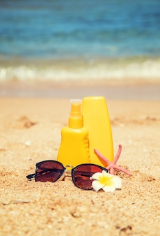 Botellas de protector solar y una estrella de mar en la playa