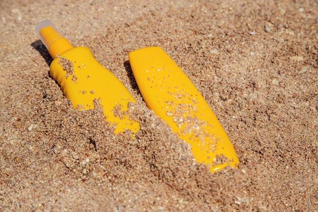 Botellas de protector solar en la playa.