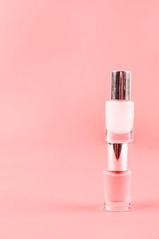 Botellas rosadas del esmalte de uñas en el fondo coralino con el espacio de la copia para escribir el texto