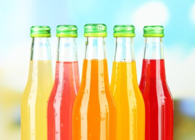 Botellas con sabrosas bebidas en brillante