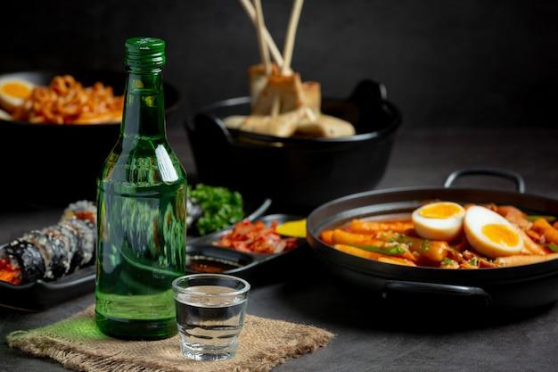 Botellas de soju y guarniciones coreanas en el menú.