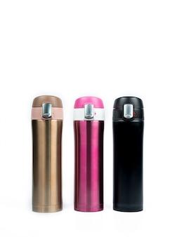Botellas de termo de oro, rosa y negro aisladas sobre fondo blanco con espacio de copia