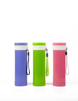 Botellas de termo púrpuras, verdes y rosas aisladas sobre fondo blanco con espacio de copia
