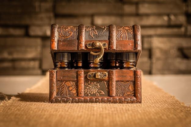 Botellas de tintura o poción en un cofre del tesoro de estilo retro. antiguo sobre fondo de tela