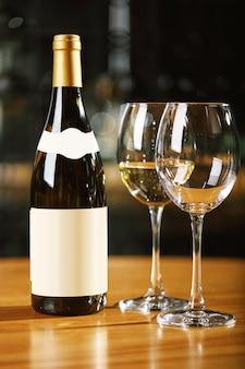 Botellas y vasos con vino en la mesa.