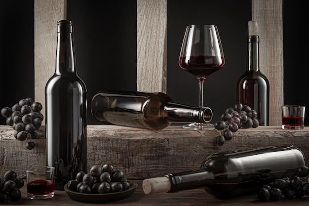 Botellas y vasos de vino tinto español y uvas sobre base de madera.