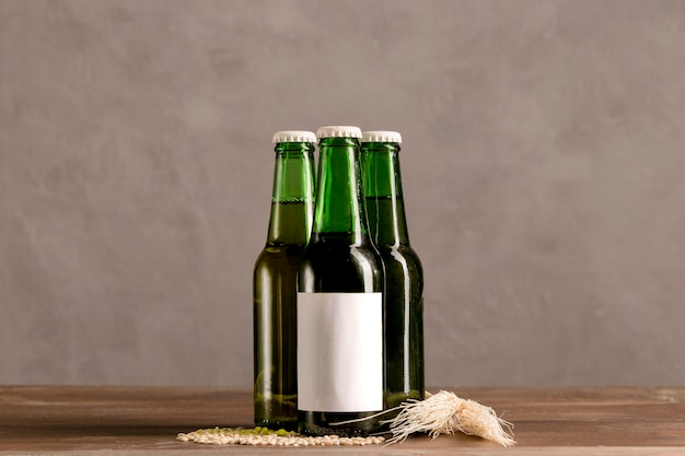 Botellas verdes en etiqueta blanca en mesa de madera