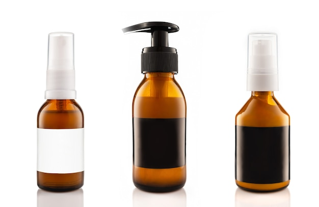 Botellas de vidrio ámbar cosmético oscuro con etiquetas en blanco negras para cosméticos aislados sobre fondo blanco.