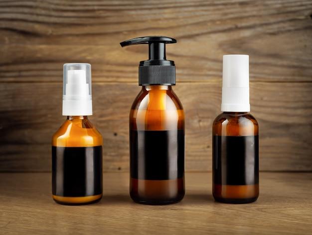 Botellas de vidrio ámbar cosmético oscuro con etiquetas en blanco negras para cosméticos en una pared de madera.