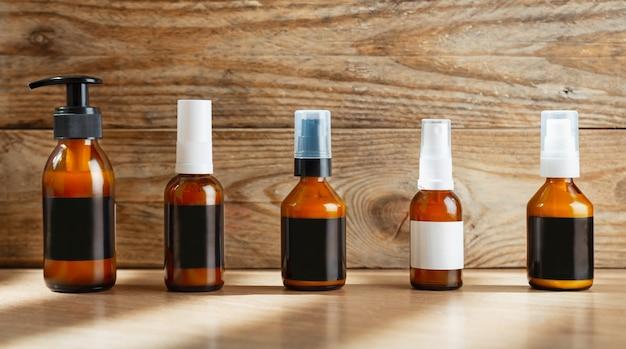 Botellas de vidrio ámbar cosmético oscuro se oscurecen con etiquetas en blanco para cosméticos en una pared de madera.