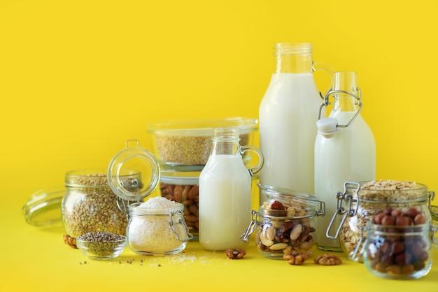 Botellas de vidrio de leche de planta vegana y almendras, nueces, coco, leche de semilla de cáñamo sobre fondo amarillo.