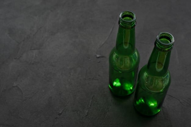 Botellas de vidrio vacías en superficie negra
