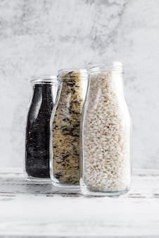 Botellas de vidrio con varios tipos de arroz en la mesa