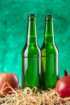 Botellas de vidrio de vista frontal con granadas en el escritorio verde beben fotografías en color de limonada