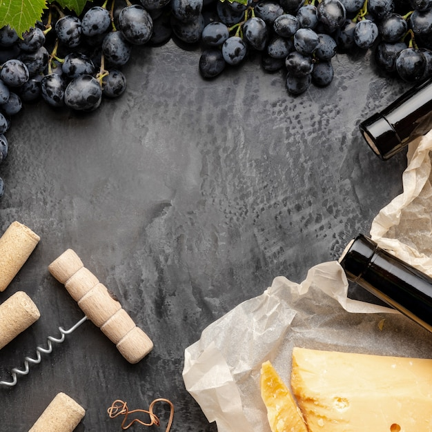 Botellas de vino quesos uvas sacacorchos marco. composición de vino de bodegón vintage con uvas camembert. espacio de cena de restaurante para texto sobre fondo de hormigón oscuro. foto común cuadrada.