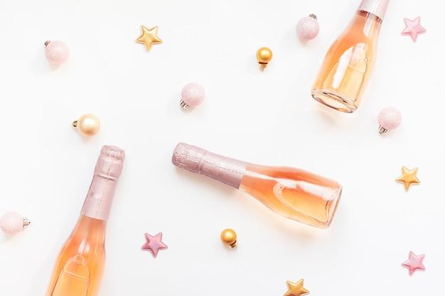 Botellas de vino rosado champagne sobre fondo blanco.