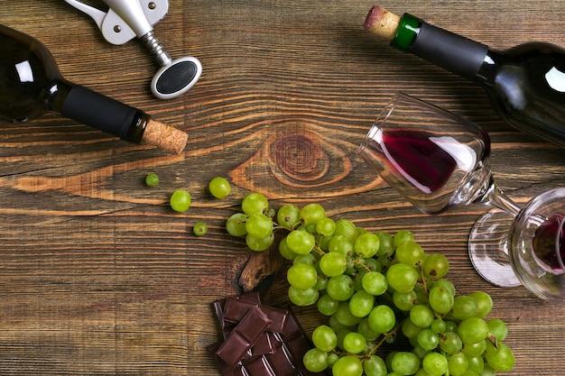 Botellas de vino tinto y blanco, chocolate de uva y vasos sobre la vista superior de la mesa de madera con espacio de copia