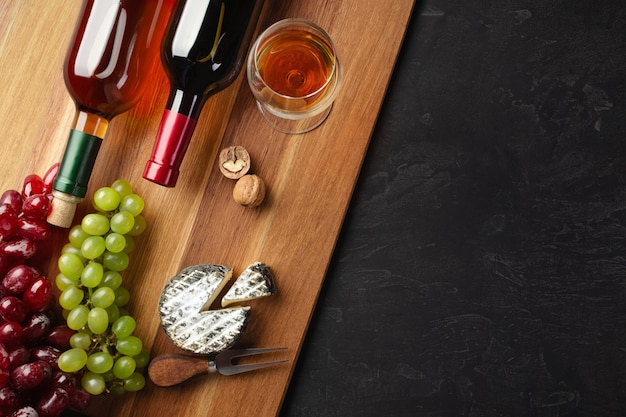 Botellas de vino tinto y blanco con racimo de uvas, cabeza de queso, nueces y copa de vino sobre tabla de madera y fondo negro con copyspace