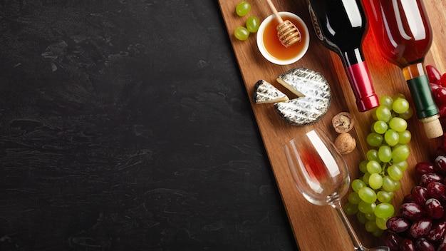 Botellas de vino tinto y blanco con racimo de uvas, queso, miel, nueces y copa de vino sobre tabla de madera y fondo negro con copyspace