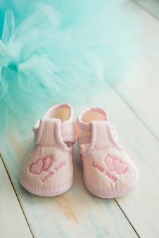 Botines rosas para bebé recién nacido sobre un fondo turquesa de madera