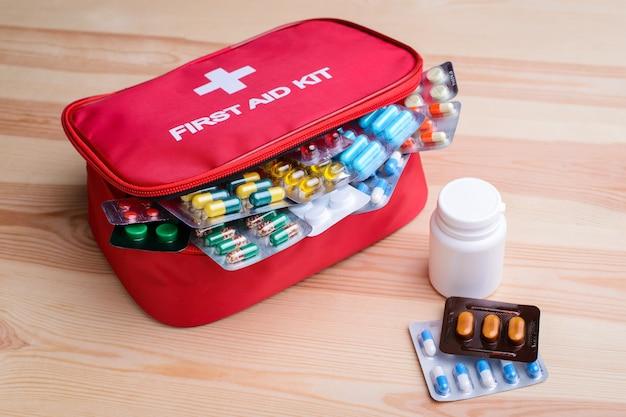 Botiquín de primeros auxilios con cápsulas y pastillas de colores en la mesa