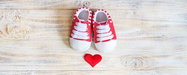 Botitas de bebé y corazón sobre un fondo claro