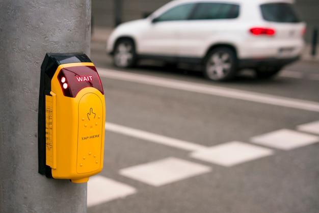 El botón de cruce de calles peatonales y la luz esperan con el auto en movimiento en el fondo