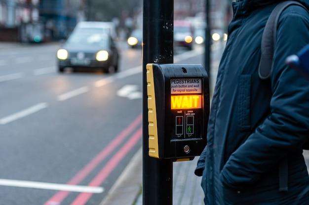 Botón de cruce peatonal para peatones con luz de advertencia en una calle desenfocada