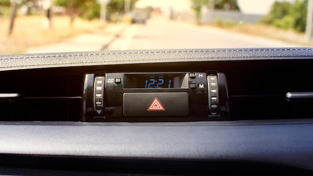 Botón de luz de emergencia del coche y pantalla digital del reloj en un coche.