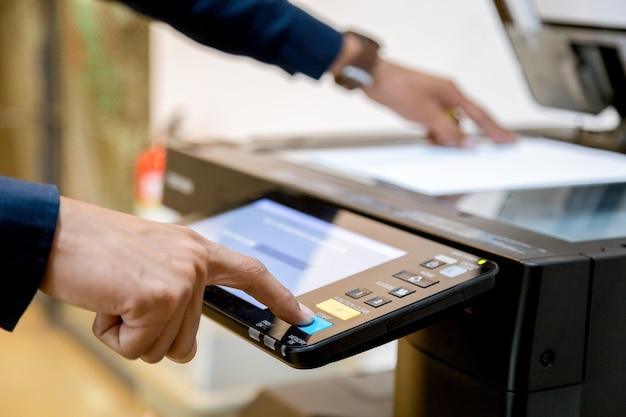 El botón de la mano del hombre de negocios en el panel de la impresora, fuentes de la máquina de la copia de la oficina del laser del escáner de la impresora comienza concepto.