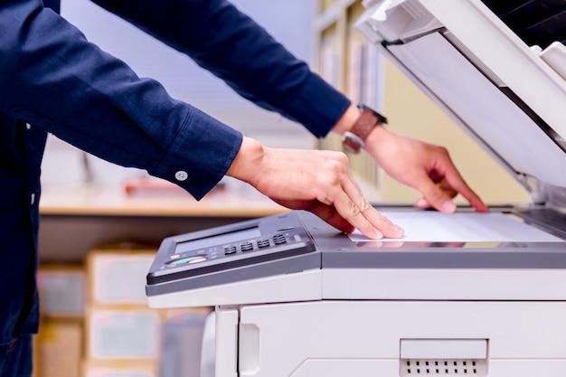 El botón de la mano del hombre de negocios en el panel de la impresora, suministros de la máquina de la copia de la oficina del laser del escáner de impresora comienza concepto.