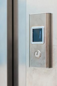 Botón metálico de ascensor con pantalla electrónica.