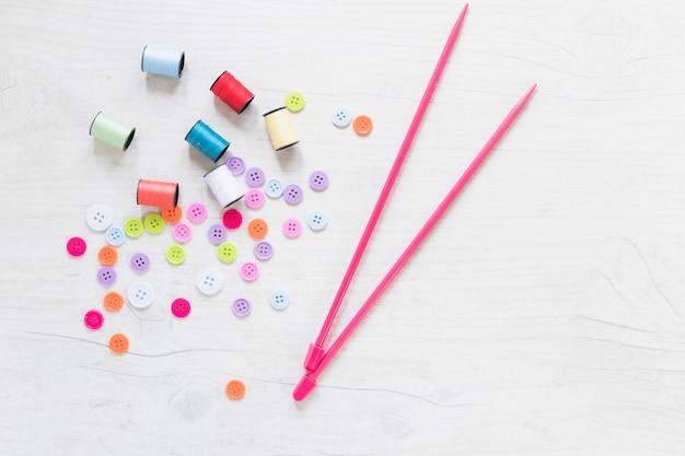 Botones de colores y carrete con agujas de punto rosa sobre fondo blanco con textura