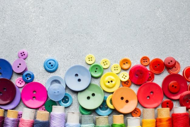 Botones de colores y rollos de hilo con fondo de espacio de copia