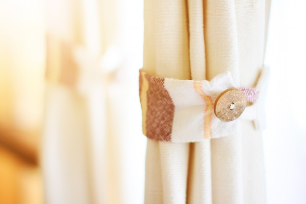 Botones de madera en cortinas blancas