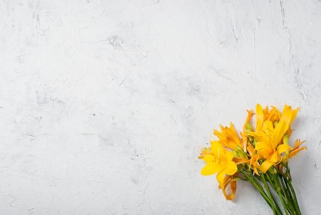Bouquet de lirios amarillos sobre hormigón.