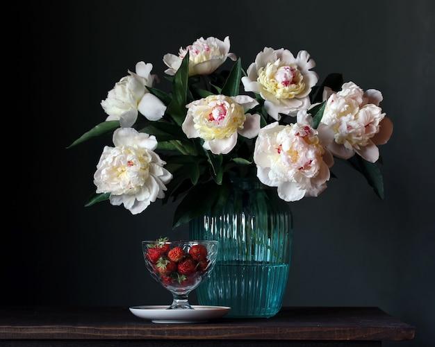 Bouquet de peonías blancas en jarrón de vidrio y fresas.