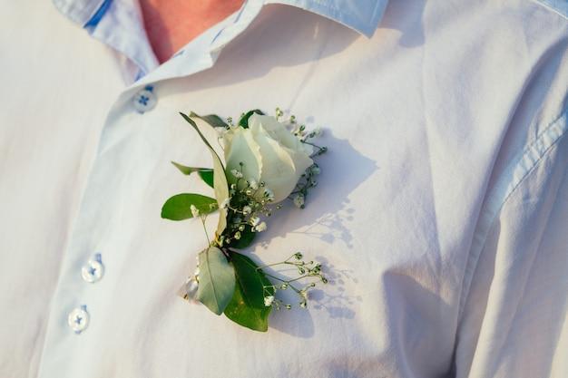 Boutonniere de una rosa blanca en la camisa de un novio