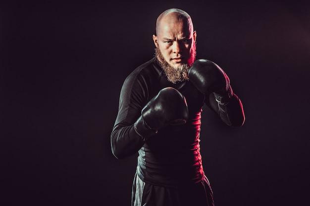 Boxeador barbudo agresivo en el espacio oscuro en estudio